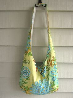 Hobo - sling bag. 100 percent cotton. Floral and butterfly print with zippered internal pocket.