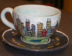 For this mug, they used a stamp of a city skyline & painted in the building colors & the sky. A highway circles around the saucer's edge.