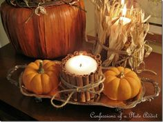 DIY Fall candle with cinnamon sticks and twine. probably glue too. This display looks so easy the candles, and tray from dollar tree, the mini pumpkins, cinnnamon sticks, and corn from your local farm/market/backyard and who doesnt have some twine lying around. Target has some cute decorative pumpkins made from light cardboard, those would also look good in this display.