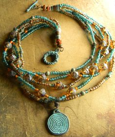 Boho blend of colors in a multi-strand necklace design with a Mykonos maze pendant focal piece. Five strands including English cut Czech glass in amber and turquoise, topaz and antique aqua seed beads, and tiny accents of terrracotta colored faceted Czech glass and solid copper heishi beads. The pendant, joining cones and toggle clasp are all Mykonos verdigris patina copper finish over Greek pewter. Total length is 17 inches, plus a 2 inch pendant drop.  All my jewelry is 100% workmanship…