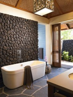 Random-pattern natural slate floors, an organic black lava rock wall, and sliding louvered wood doors opening onto a private terrace give this Hawaiian bathroom a luxurious outdoor feel  (via Hawaii - contemporary - bathroom - hawaii - by Dara Rosenfeld Design)