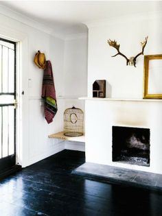 Fireplace, white walls and black floorboards