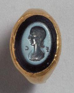 Fingerring mit Gemme: Büste der Plautilla  Römisch, Späte Kaiserzeit   203 - 205 n. Chr.   Gold; Nicolo, graublaue auf tief dunkelblauer Schicht    H. 1,35 cm, B. 0,95 cm, Dm. (Ring) 2,45 cm, Gew. 14,97 g     In die Ringplatte des massiven antiken Goldringes ist eine Nicologemme mit weiblicher Büste im Profil eingesetzt. Dargestellt ist Fulvia Plautilla (gest. 211 n. Chr.), die Gemahlin des Kaisers Caracalla (reg. 211 - 217 n. Chr.)