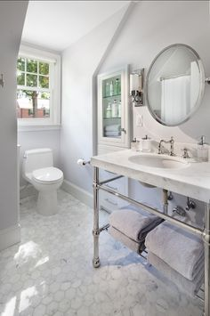 Carrara marble hex tiles and metal washstand with marble countertop.