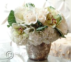 A rustic vintage silver vase decorated with a pave of white hydrangeas, kale, cream vendella roses and scatters of green cymbidiums.  Sold of of this container.  No wonder--great.  Chic in vintage