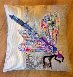 Neutral cream background, with an appliqued handmade purple Dragonfly Cushion.