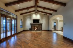 Luxury Italian Villa custom home living room with dark wood flooring and fire place