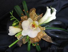 Wrist corsage featuring mini phaleonopsis orchid, mini callas and freesia.