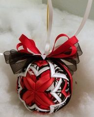 "Black, Red, and White Cathedral handmade quilted ornament:    This 3"" handmade quilted ornament is made with red satin, white satin ribbons and layered with black, red, and white fabrics. It is layered in the cathedral pattern. The final quilted ornament, not including the bow and ribbon loop, measures approximately three inches in diameter. This ornament would look charming in your favorite bowl or basket or as a decoration in a room. It will make a great Christmas tree decoration! It makes…"