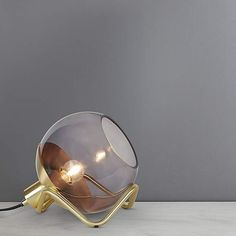 Featuring a Daniel Savage design, this stunning table lamp features a smoke glass sphere shade with satin brass finishing and a unique base. Suitable for use wi. Home Decor Lights, Glass Ball, Wall Lights, Table Lamp, Brass, Smoke, Mirror, Design, Living Room