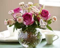 An absolutely stunning arrangement of blushing silk roses in a clear globe vase