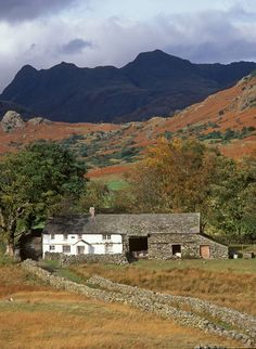 Langdale - Little Langdale farm. Traditional whitewashed 18th century farmstead with Langdale Pikes in background