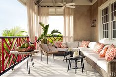 Love the color on the railing. The veranda is furnished with a vintage French rattan chair and an RH sectional sofa and curtains; the low tables are by IKEA