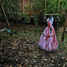 A Halloween costume / blood soaked dress hangs on a swing set in the back yard. Photo by @dguttenfelder by everydayusa