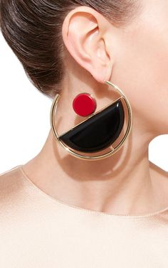 These bold **Marni** hoop earrings feature a striking modernist design in gold-plated brass and lightweight methacrylic.