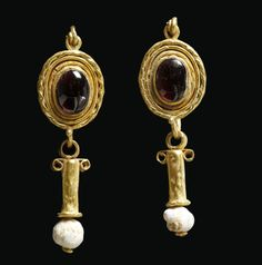 Ancient Roman gold and garnet earrings, each with a white bead at the end, dating to the 1st to 2nd centuries CE.