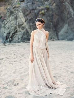 Long informal chiffon dress is crafted with soft chiffon fabric. Sleeveless halter blouson bodice features crossed scarf and keyhole on back. A-line skirt with sweep train finishing off the look.