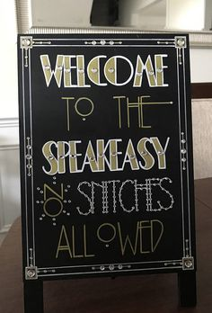 Having a Roaring Twenties themed or Great Gatsby wedding?! Want to add some glitz, glamour, and that chic extra touch to your evening party event?! Then you need a custom created sign!!! This Speakeasy Welcome sandwich board sign was designed with your occasion in mind. Spice up your wedding or party table décor using this fun Art Deco font inspired sign. This 8 x 10 self-standing sign has been painted all black and features freehand lettering and intricate designs. It is littered with…