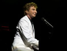 """Sitting down at the piano, Barry Manilow serenades the crowd with the classic Billboard Hot 100 Number One hit, """"I Write the Songs.""""(© David Gordon)"""
