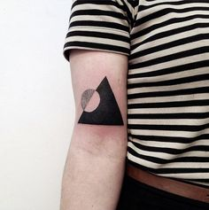 This tattoo also seems to depict a mountain with a sun/moon inset, transforming an earth motif into a perfectly neat and bold geometric tattoo.