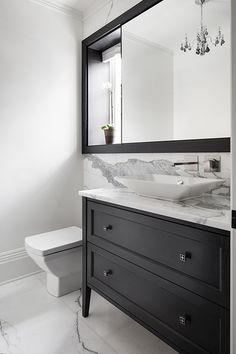 Black and white luxury bathroom with marble countertop and wall.