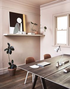 Modern workspace with dusty pink walls, a floating shelf styled with mod art and indoor plants, and a wooden table doubling as a desk