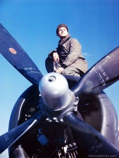 A member of the First Brazilian Fighter Squadron poses on top of a P-47 Thunderbolt motor at an airfield somewhere in Italy.