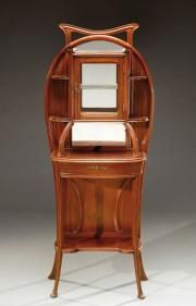 OUIS MAJORELLE, attribué à Vitrine d'exposition en acajou à corps nervuré et mouluré ouvrant en ceinture par deux tiroirs secrets sur les côtés et une tablette coulissante gainée de cuir rouge et en partie haute par une porte vitrée flanquée d'étagères ouvertes à fond miroir. Elle repose sur un piétement galbé végétal. Vers 1900. H: 150 cm L: 61 cm P: 28 cm