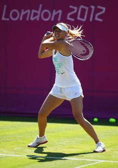 Maria Sharapova Photos Photos - Maria Sharapova of Russia plays a backhand in a practice session during previews ahead of the 2012 London Olympic Games at the All England Lawn Tennis and Croquet Club in Wimbledon on July 23, 2012 in London, England. - Olympics - Previews - Day - 4