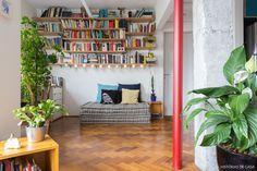 Prateleiras sustentadas por mãos francesas e futons com almofadas que servem como sofá.