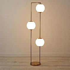 Shop Cosmos Floor Lamp.  The three glowing orbs on this unique floor lamp are suspended by a simple metal frame, ready to cast a warm glow in your bedroom, living room or playroom.