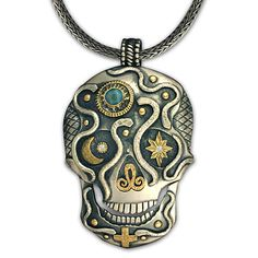 "Just in time for Day of the Dead and All Hallows' Eve, this one-of-a-kind skull pendant was handmade by the Lead Designer of Reflective Jewelry. Helen says she enjoys this time of year because ""It's the time when those that have passed come closer. A liminal time. A time to celebrate with our ancestors."" This particular skull was made with an ethically sourced Fair Trade gold, recycled sterling silver, and is adorned with a blue moonstone and an illustrious diamond."