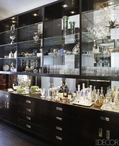 The bar's custom cabinetry, lacquered in Benjamin Moore's Black Ink, holds family heirlooms, including tennis trophies and jade objects. - ELLEDecor.com