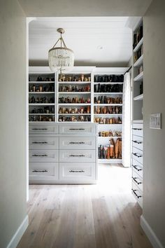 A fashionista's dream, this white custom walk-in closet features light gray wash wood floors fixed framing a white island fitted with white drawers donning ornate black pulls. Walk In Closet Small, Walk In Closet Design, Small Closets, Dream Closets, Closet Designs, Wardrobe Design, Placard Design, Closet Island, Closet Drawers