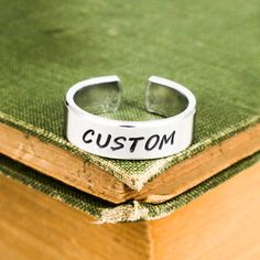 Have a cool idea for a personalized ring? Look at the 2nd and 3rd photos in the listing to select your font and any design stamp you might like. There will be a place to leave a note on your order during checkout, so please leave a detailed note for your idea. If we have any issues, questions or suggestions we will send you a message to clear things up. Feel free to send us a message too, if you need any help getting your design together.  This ring is stamped on a 1/4 wide aluminum blan...