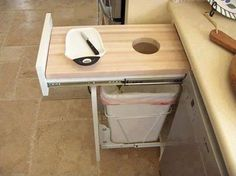 BRILLIANT!!!  over trash cutting board that hides in the cabinets?!  woo!!
