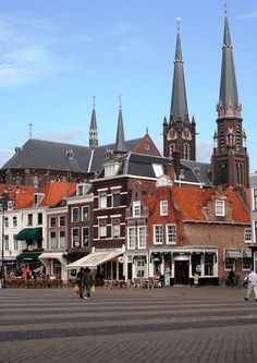 The Maria van Jessekerk steeples tower over surrounding buildings in Delft old town.  Find information about this church and others in South Holland (NL) here https://www.angloinfo.com/south-holland/directory/south-holland-churches-religion-spirituality-23