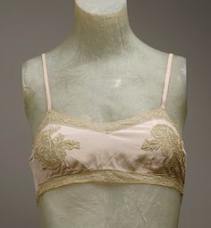 : The bra in the 1920's wasn't meant to draw attention to the breasts but rather to flatten them and make them inconspicuous. A bra was little more than a bandeau with shoulder straps. Nevertheless they were dainty pieces in sheer silk or cotton