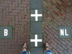 standing with one leg in the Netherlands and one in Belgium ...