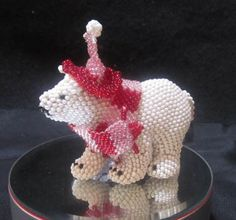 "Darrell Saracino, Zuni, beaded polar bear, with pink and red beaded scarf and cap. 2 1/4""  Sold"