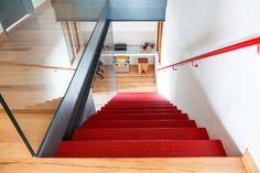 Decoração de apartamento moderno, escandinavo, branco. Escada vermelha, corrimão vermelho e parede branca.