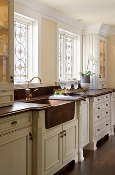 Those stained glass windows! Copper Farmhouse Sink! Furniture details on the cabinets! Love the whole room