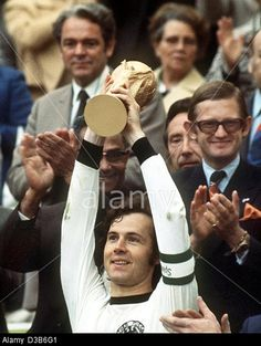 Franz Beckenbauer, then German team captain, happily lifts the 'Coupe Jules Rimet' after winning the Soccer World Cup in Munich, 7 July 1974. © dpa picture alliance / Alamy
