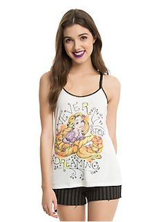 """<p>Do you have a dream? Whether its becoming a concert pianist, making a love connection, or seeing the lanterns gleam, never give up on that dream. It could be right around the corner for you! Cream tank top with black crocheted racerback straps from Disney's <i>Tangled</i> with an image of Rapunzel and text design that reads """"Never Stop Dreaming.""""</p>  <ul> <li>87% polyester; 9% rayon; 4% spandex</li> <li>Wash cold; dry low</li> <li>Imported</li> <li>Listed in junior sizes</l..."""