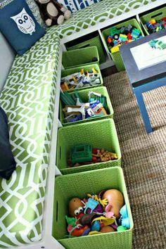 Ikea kast met bakken voor speelgoed. Bovenop een kussen om lekker te zitten.