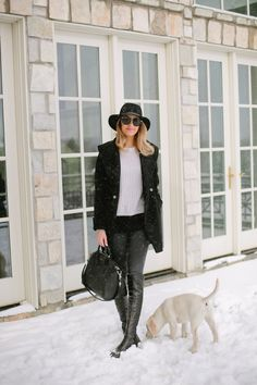 Emily Jackson looks effortlessly chic in this black and white winter combination of skinny black jeans, a white cropped sweater, a black overcoat and leather knee boots. Add a wide brim hat or fedora to recreate this look exactly. Sweater: Vince, Jeans/Jacket/Hat: Rag & Bone, Bag: Givenchy, Boots: Stuart Weitzman.