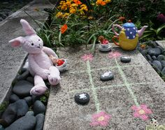 Fun DIY garden tea party Tic Tac Toe game | painting rocks is probably as old as paint but it doesn't make it any less fun, so here is a project where kids can wear their creative hats and paint their own Tic Tac Toe pieces on rocks and then make their own board outside using sidewalk chalk.