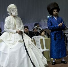 The bride holds a gartel while family members dance and thegrandson of the Rabbi of the T...