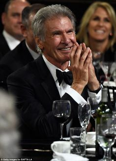 Suave: Harrison looked typically dapper in a black tuxedo as he laughed with the crowd