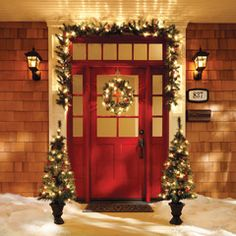 Evergreen boughs in strings of outdoor lights hung around a front door